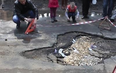 Автолюбители Приморья засыпали дорожную яму деньгами