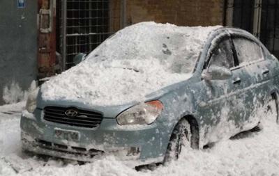 В центре Киева глыба снега сплющила автомобиль