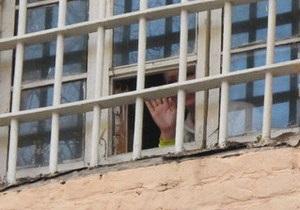 Фотогалерея: Улыбается и машет. Тимошенко выглянула из окна СИЗО
