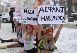Асфальт накрылся: Днепропетровские активистки FEMEN сели на шпагат, чтобы  прикрыть ямы на дороге