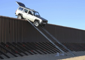 На границе США и Мексики джип нелегалов застрял на четырехметровом заборе