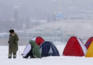 В Киеве сотни добровольцев делают проруби в водоемах, чтобы спасти рыбу от удушья