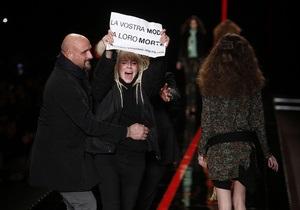 Неделя моды в Милане: активистка выбежала на подиум с плакатом Ваша мода - их смерть