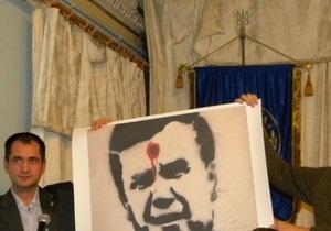 На языковом форуме в Киеве растянули баннер с изображением Януковича с красной точкой на лбу