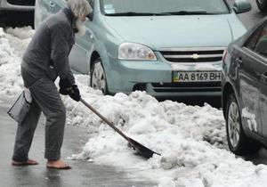 В центре Киева неизвестный мужчина босиком убирает снег