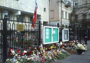 Люди несут цветы к польскому посольству в Киеве