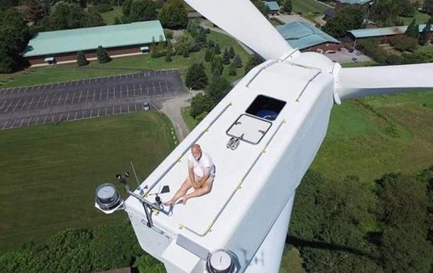 Дрон заснял загорающего на верхушке ветрогенератора мужчину