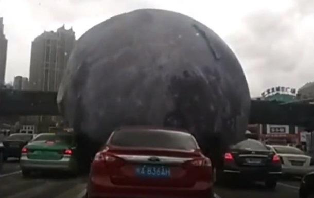 ВКитайской республике немалый «лунный» шар развеселил водителей, прокатившись покрышам авто