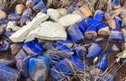 Тисячі каністр з невідомою речовиною викинули в річку під Києвом