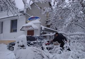 Снегопад в Киеве: Деревья падают на автомобили